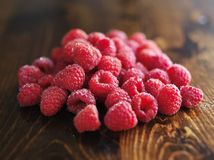 Pile of raspberries on wooden table. Shot with selective focus Stock Photo