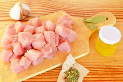 Pile of raw beef chunks on the wooden cutting board, garlic, spices, olive oil. Raw chopped meat. Raw meat cubes Stock Photos