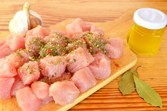 Pile of raw beef chunks on the wooden cutting board, garlic, spices, olive oil. Raw meat photo. Sliced raw meat. Meat slices photo Royalty Free Stock Photography