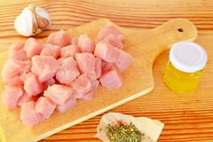 Pile of raw beef chunks on the wooden cutting board, garlic, spices, olive oil. Pieces of meat. Meat cut into cubes. Meat is diced. Meat is ready for cooking Stock Image