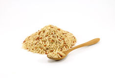 Pile of raw brown rice with wooden spoon on white background Stock Images