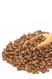 Pile of raw coffee beans with wooden spoon.  Royalty Free Stock Photography