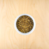Pile of raw dry brown lentils in cup, top view. Square composition, food preparation, copy space Royalty Free Stock Photo
