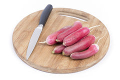 Pile of raw fresh red radishes on the wooden board.  Royalty Free Stock Images