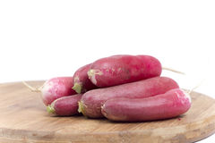 Pile of raw fresh red radishes on the wooden board.  Stock Photo