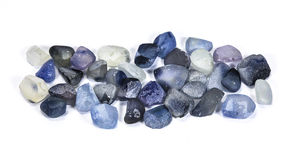 Pile of raw natural blue sapphires. On white background Royalty Free Stock Photos