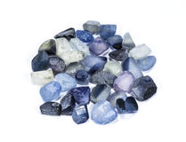 Pile of raw natural blue sapphires. On white background Stock Photo