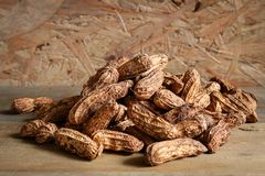 Pile raw peanuts in shell on wooden background. Raw peanuts in shall Stock Images