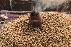Pile of raw peanuts on a street market in India. With a smoking pot. Peanuts fried in the street. Indian way of roasting peanuts. The street food Stock Photos