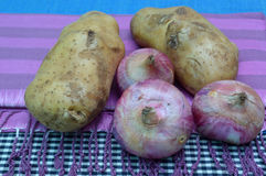 Pile of raw potato and red onion. On tablecloth Stock Photo