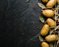 A pile of raw potatoes on a dark stone background. Preparation of soup or potato dishes. Copy space Stock Photography