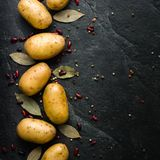 A pile of raw potatoes on a dark stone background. Preparation of soup or potato dishes. Copy space Royalty Free Stock Photos