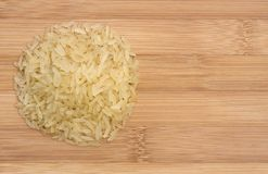 Pile of raw rice on wooden table Royalty Free Stock Image