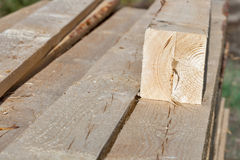 Pile of rectangular wooden beams in the construction site. Stock Photos
