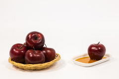 Pile of red apples and red apple on white plate with honey isola Royalty Free Stock Photography