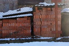 A pile of red bricks on a construction site behind a metal mesh fence in white snow. Outside royalty free stock photos
