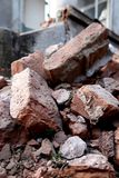 Pile of red bricks from demolished house in focus Royalty Free Stock Image