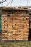 Pile of red bricks neatly folded on pallets. lot of brick for construction is covered from rain. Building material for walls,. A pile of red bricks neatly folded stock photos