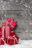 Pile of red Christmas presents, with snow on grey wooden backgro Royalty Free Stock Image