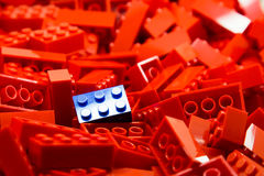 Pile of red color building blocks with selective focus and highlight on one particular blue block using available light Royalty Free Stock Image