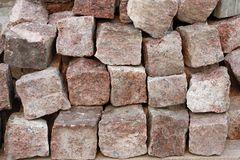 Pile of red granite cobblestones on a palette are ready to be laid in the sidewalk Royalty Free Stock Photos