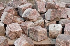 Pile of red granite cobblestones on a palette are ready to be laid in the sidewalk Royalty Free Stock Images
