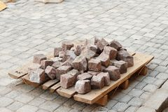 Pile of red granite cobblestones on a palette are ready to be laid in the sidewalk Stock Images