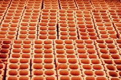 Pile of red hollow bricks with large holes forming lines in repeating geometric pattern Royalty Free Stock Photo