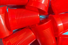 Pile of red plastic drinking cup on blue background. Environmental protection plastic-free alternatives nature friendly living. Hard light harsh shadows stock image