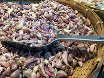 Pile red raw onion cloves on the metal scoop in the bamboo basket. royalty free stock image