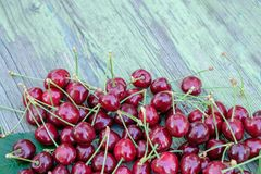 A pile of red ripe merry cherries on the old wooden table. Healthy seasonal berries. Royalty Free Stock Photography