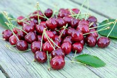 A pile of red ripe merry cherries on the old wooden table. Stock Photo
