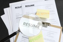 Pile of resume templates and sticks on it, black background. HR made decision and approved one candidate and rejected to another.P stock photos