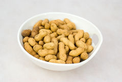 Pile of ripe crude peanuts in white bowl Royalty Free Stock Images