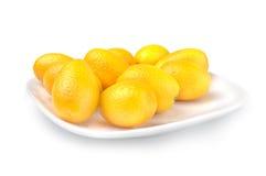 Pile of ripe kumquat on plate over white background Stock Photos