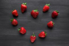 Pile of ripe strawberries on black background with copy space. Ripe fresh strawberries in the shape of a heart on a black wooden table. summer fruits and berries royalty free stock image