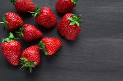 Pile of ripe strawberries on black background with copy space. Ripe fresh strawberries on a black wooden table. summer fruits and berries. The concept of a stock photos
