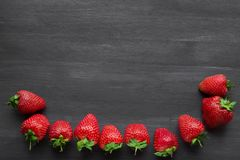 Pile of ripe strawberries on black background with copy space. Ripe fresh strawberries on a black wooden table. summer fruits and berries. The concept of a stock image