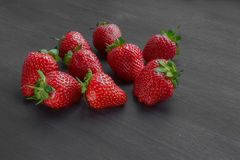 Pile of ripe strawberries on black background with copy space. Ripe fresh strawberries on a black wooden table. summer fruits and berries. The concept of a royalty free stock photography