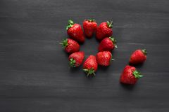 Pile of ripe strawberries on black background with copy space. Ripe fresh strawberries on a black wooden table. summer fruits and berries. The concept of a stock photography