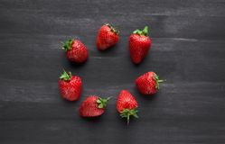 Pile of ripe strawberries on black background with copy space. Ripe fresh strawberries on a black wooden table. summer fruits and berries. The concept of a stock images