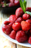 Pile ripe strawberries on a white plate Royalty Free Stock Photos