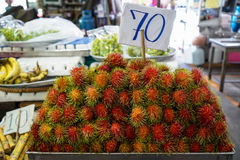 Pile of ripe sweet reddish rambutan fruit with pliable green hair in local market atmosphere. Thailand stock image