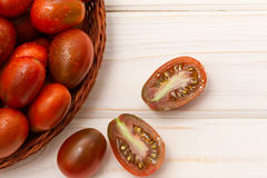 Pile of ripe tomatoes. (Cherry, Black Prince) on wooden background Royalty Free Stock Photography