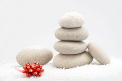 Pile of river stones and a red bow on top of it. Pile of river stones in the snow and a red bow on top of it Royalty Free Stock Image