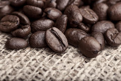 Pile of roasted black coffee. Large coffee beans lying on canvas selective focus stock photos