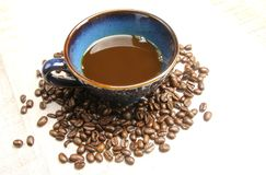 A pile of coffee beans around a cup royalty free stock photography