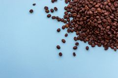 Pile of roasted dark brown coffee beans on blue background with copy space. Aroma drink concept. Breakfast background. Coffee closeup with copy space royalty free stock photography
