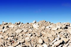 Rock Rubble Hardcore Blue Sky. Pile of rock rubble hardcore background with a blue sky and copy space for construction ecology ideas and designs Stock Photo