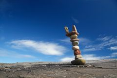 Pile of rocks. Column of balanced boulders against blue sky stock images